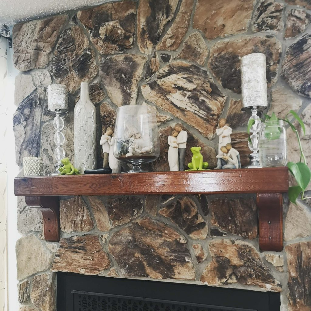 This fireplace mantel has been freshened up with a pop of lime green, natural elements, and a touch of plant life with a sweeping vine. inspireddecorator.com