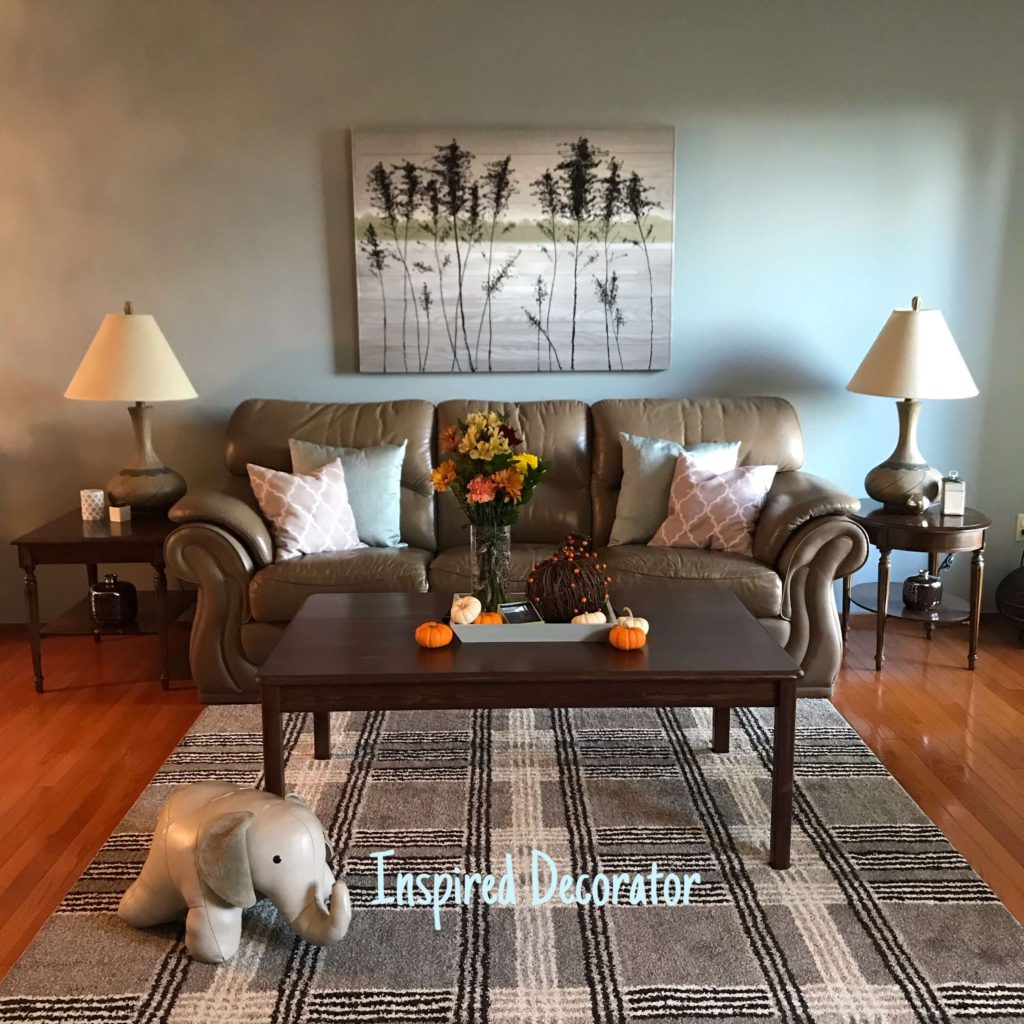 A living room is sparsely decorated for the fall season. The fall decor add pops of color to the room but otherwise the regualr decor and design style are still the most prominent.