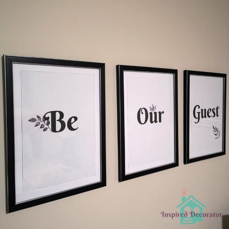 Be Our Guest wall art is displayed in the guest room. They are framed in large black picture frames. Print it at home on computer paper. DIY wall art! Free Be Our Guest printable download is available! www.inspireddecorator.com