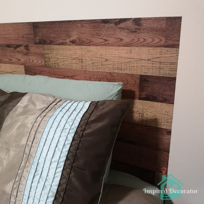 DIY headboard to get a wood plank look. Budget friendly headboard made using dollar store vinyl decals. This headboard was made for under $15! www.inspireddecorator.com