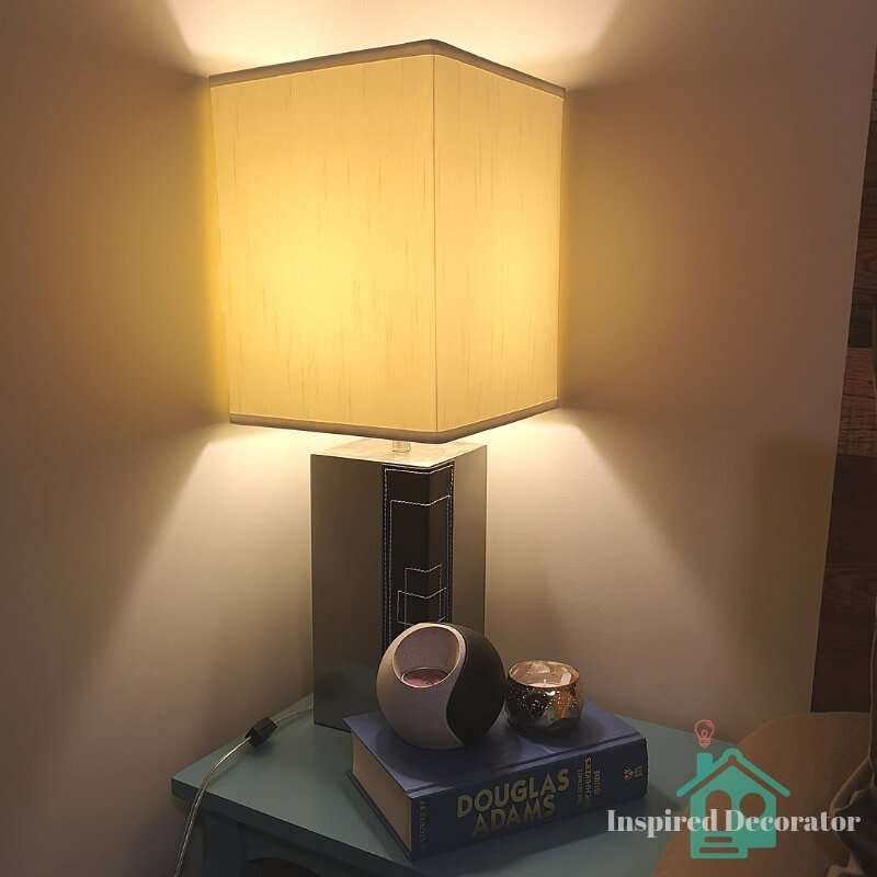 A simple table lamp functions as a bedside lamp. It has a square lampshade so it fits perfectly into the corner of the room. It is one of five light sources in the room www.inspireddecorator.com