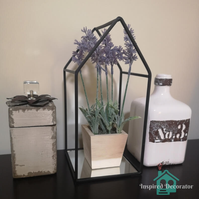 This farmhouse inspired display is a cute nod to a rustic glam design style. It is a bit farmhouse style with the distressed edging on the containers and the lavender plant, but the crystal knob and mirror base brings some glam to the collection. www.inspireddecorator.com
