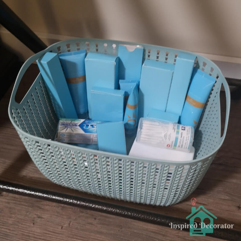 The guest room is always stocked with extra travel-sized toiletries in case an item was forgotten at home. They are stored in a small blue basket-weave container from Dollarama. These are a must-have item for a welcoming guest room. www.inspireddecorator.com
