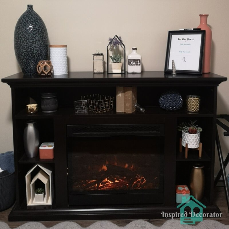 An electric fireplace brings warmth and comfort to the guest room. It is adorned with a collection of colorful, textured, and metallic decor. This decorated fireplace adds interest to the room as well as storage space for guests who are staying for longer periods of time. www.inspireddecorator.com