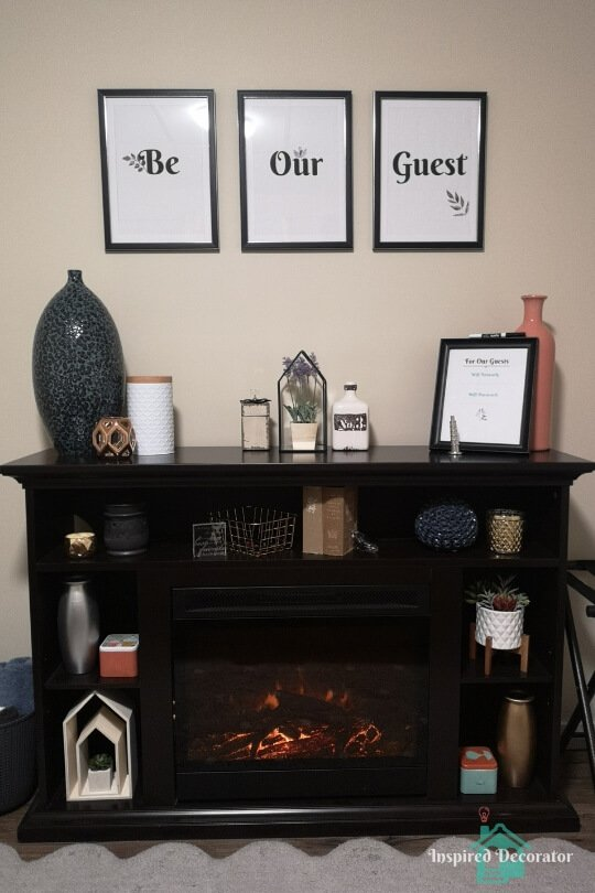 The electric fireplace sits directly across from the bed in this guest room. This DIY Be Our Guest wall sign invites guests in along with the matching wifi password printable. The fireplace is decorated with a variety of colorful and textured items to create interest in this welcoming space. The fireplace is a source of storage, warmth, and ambience in the guest room.  www.inspireddecorator.com