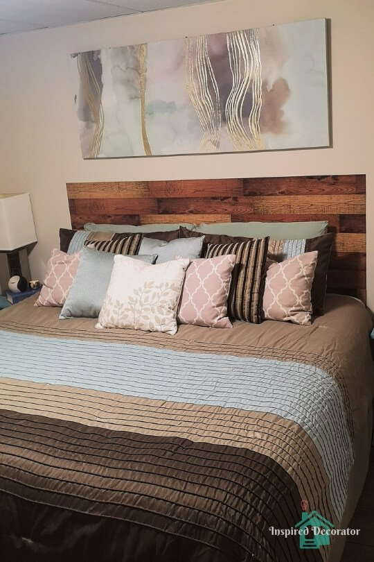 King-sized bed in a guest bedroom. It's covered with a brown and blue  comforter and an assortment of colorful pillows. Fun pillow game! The headboard looks like wood planks. www.inspireddecorator.com