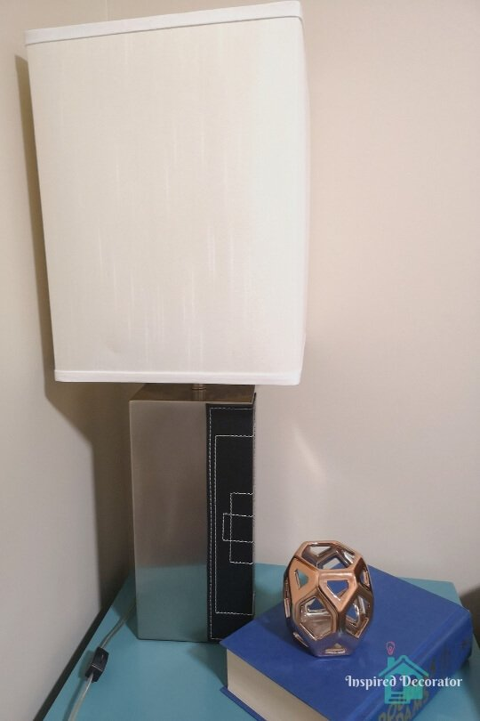 A simple silver table lamp functions as a bedside lamp. It has a square lampshade so it fits perfectly into the corner of the room. It is one of five light sources in the room www.inspireddecorator.com