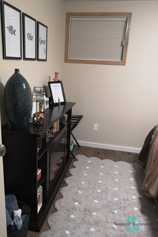 A doorway view into the guest room. They get a glimpse of the fireplace and the bed in this inviting room as soon as they come down the stairs. Find a way to welcome your guests in! www.inspireddecorator.com
