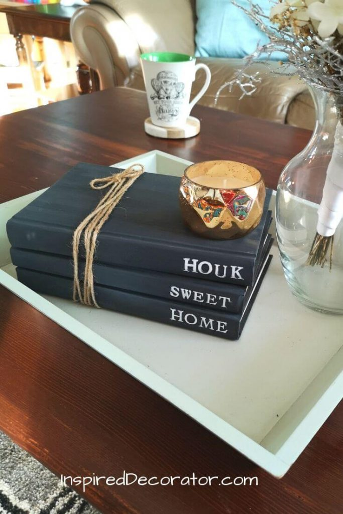 A trio of Farmhouse style DIY stamped books that are painted black. They have white words stamped on them saying Home Sweet Home.