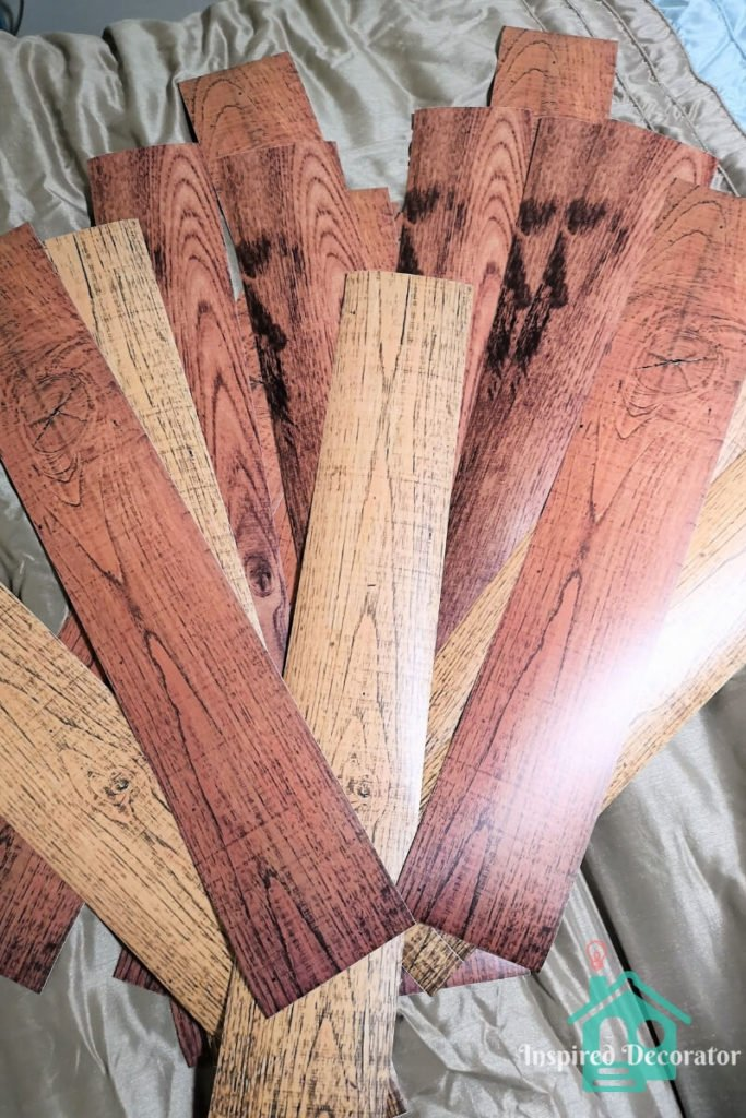 An assortment of vinyl decal plank colors were purchased for this project. The colors range from light oak, to a red oak, to a darker amber oak. Here they are spread out for full viewing. inspireddecorator.com