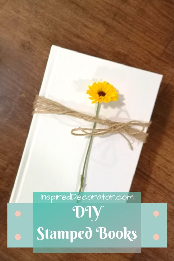 A white hardcover book that has been painted for a chalky finish and has a cheerful yellow flower tied to its front cover with brown twine