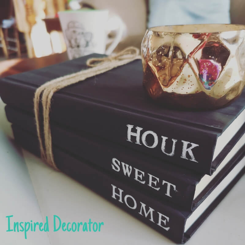 "A stack of 3 black stamped books with the words ""Houk Sweet Home"" stamped on each in white ink."