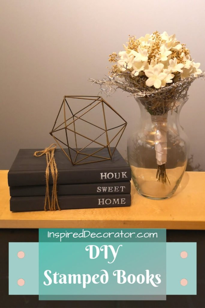 A stack of 3 stamped black books are tied with brown twine. The saying Home Sweet Home is stamped on them. They are displayed with other farmhouse decorations