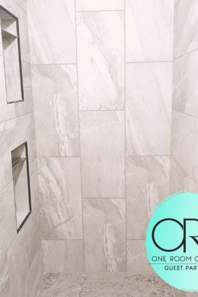 This large walk-in shower is wrapped in a light gray, rectangular tile.