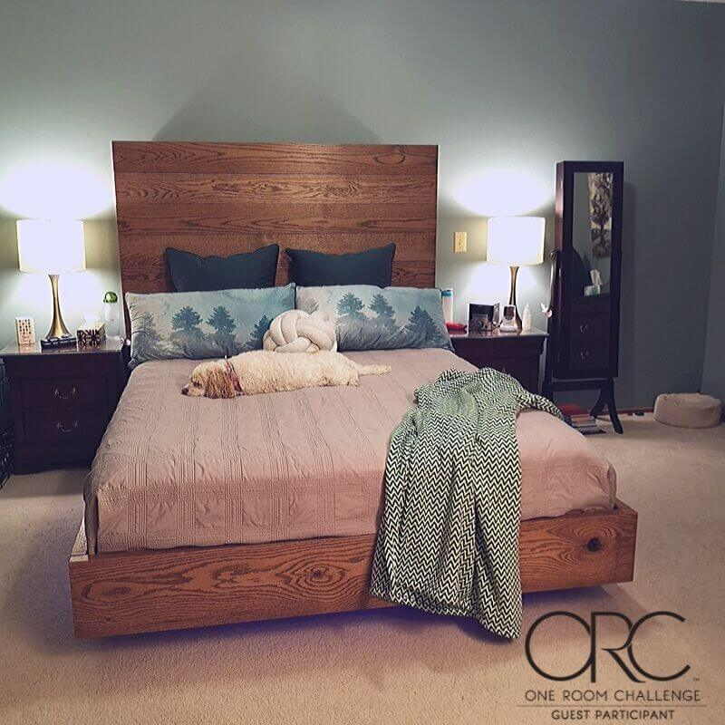 The master bedroom features a diy oak floating bedframe, a calming wall color called Stratton Blue HC-142 by Benjamin Moore, and ample space to move around.
