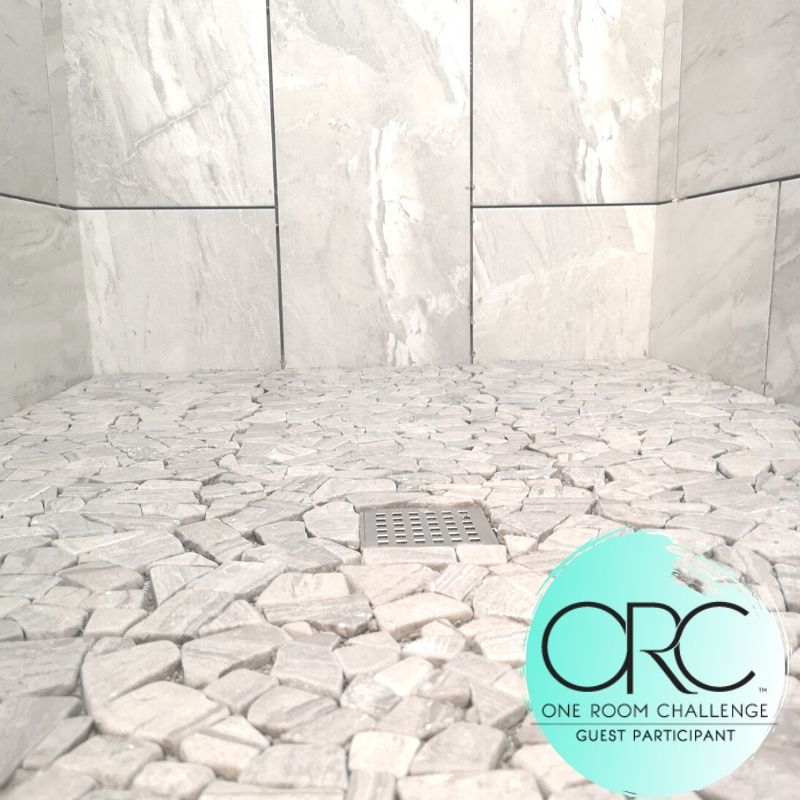 The shower tiles are a mix of porcelain and marble stone. The colors are cohesive to give the impression of wrapping around you.