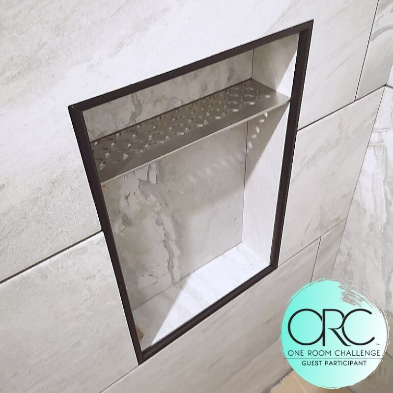 The tiled shower niches are framed in a black metal trim to make them pop. The stainless steel metal shelf has great drainage while being very sturdy.