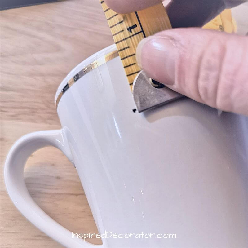To keep the letters straight, you can measure and mark dots evenly around your mug as a guidline.