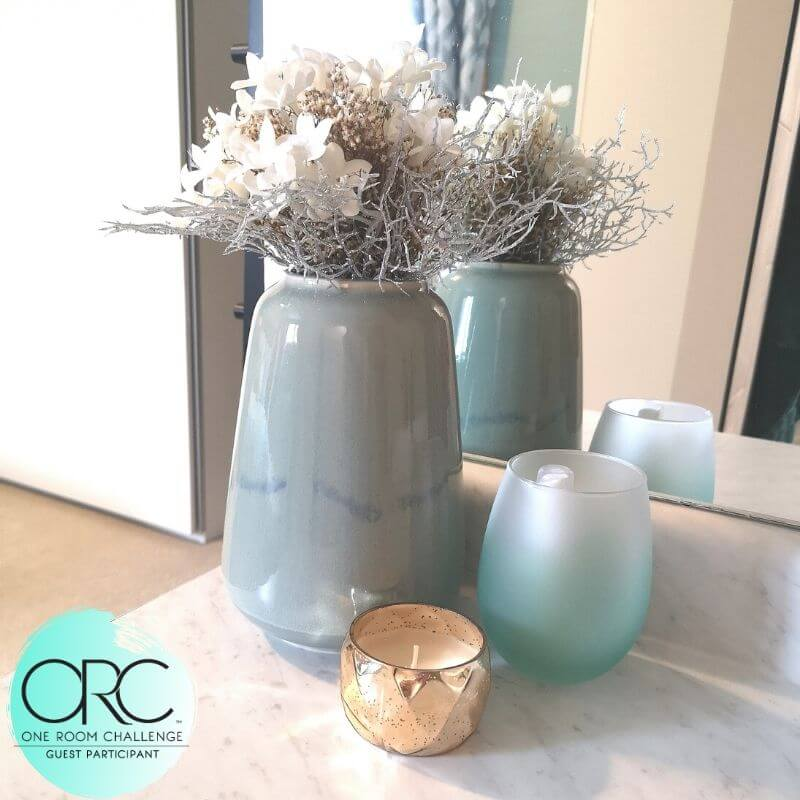 Some decorative jars in the same soothing colors as the bedroom help brighten up the master bathroom.