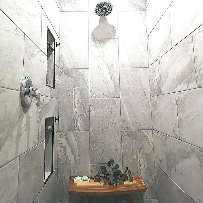 The walk-In spa shower comes to life with soft grey stone-like porcelain tiles in a wrap-around pattern.