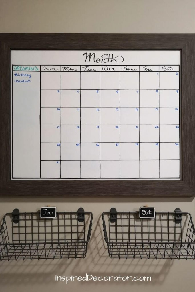 A second framed chalkboard was picked up and turned into a matching calendar. A whiteboard wall sticker was cut and adhered over the chalkboard. A permanent marker was used to draw the grid, but a whiteboard markers are used to fill in the dates, months, and schedules. - the Inspired Decorator