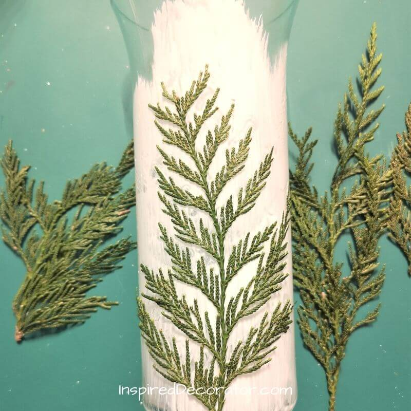 Pick your favorite foliage branches and press them onto your soon-to-be Christmas candleholder.