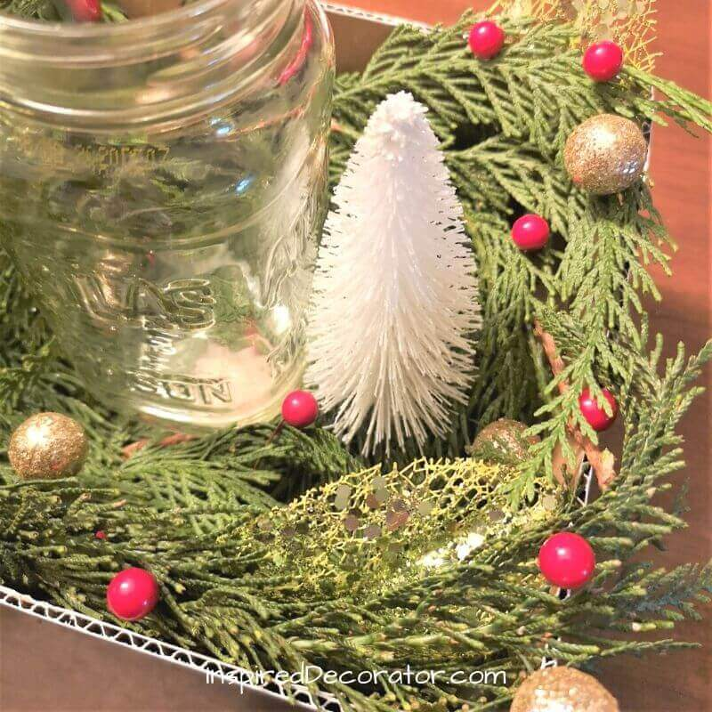 Along side the mason jar in the center, place some bottle brush Christmas trees to accent it