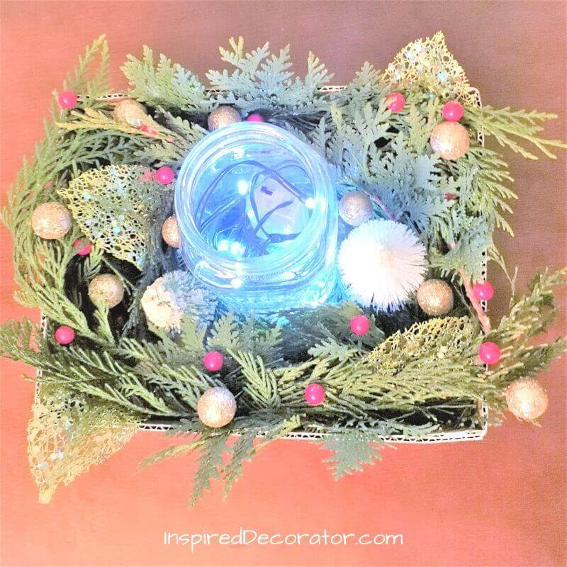 Place fairy lights inside the mason jar or weave into the pine needles around it