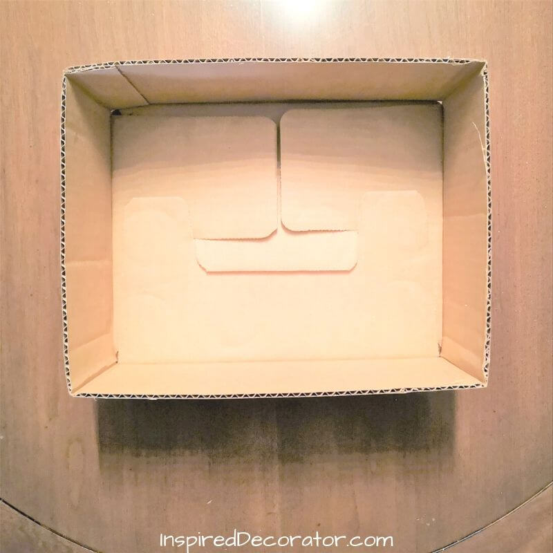 This cardboard box is cut down to size to become a container for the Christmas centerpiece. Trim off any loose pieces and make sure the bottom is secure.