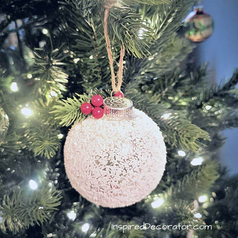 Hang your frosted Christmas ball near some twinkling lights to see it glisten. The epsom salts add sparkle to the white decoration. It's a beautiful diy Christmas ornament.