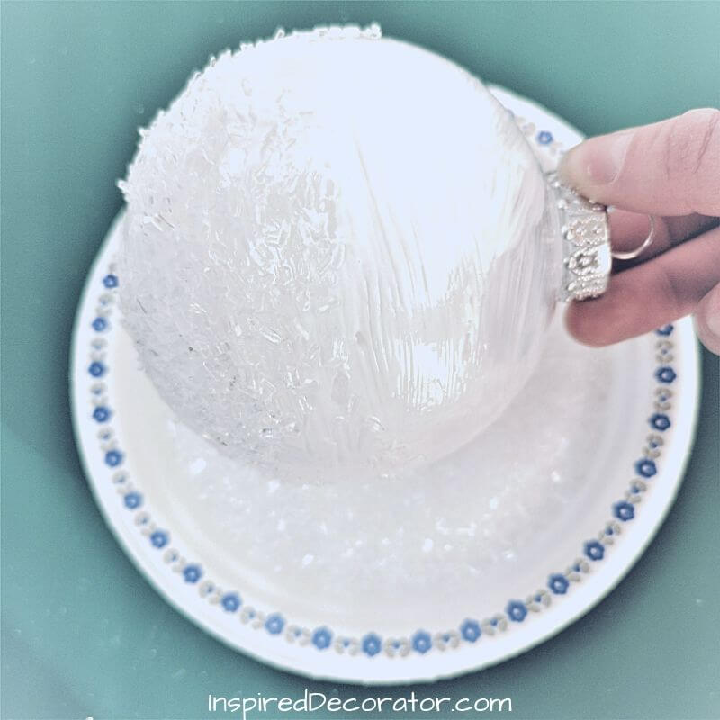 Rolling the mod podge-coated Christmas ball in a dish of epsom salt is an easy and less messy way to create a frosted Christmas ornament.