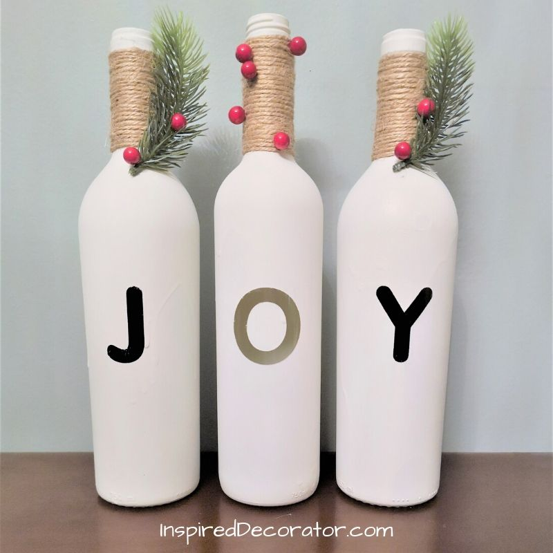 Bring Joy to the world with these diy Christmas Joy Wine Bottles display. Its a whimsical way to dress up your dining table or buffet. Using recycled bottles, spray paint and a few accessories, this fun diy is for anyone! -the Inspired Decorator
