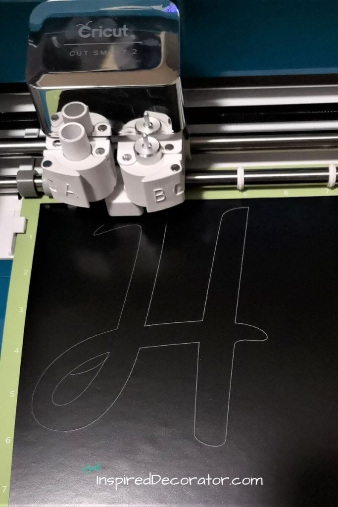 A cricut explore air 2 quickly cuts out a monogram H from this chalkboard vinyl decal (from the dollar store) to be placed on the new wine jug decor piece.