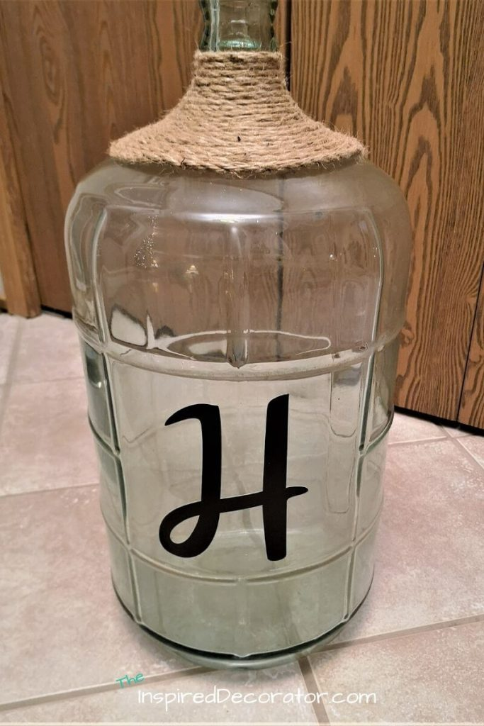 A fun and easy to customize diy project using jute rope, hot glue, and a monogram decal. This wine jug decor now is a staement piece in the entryway of this rustic style home.- the Inspired Decorator