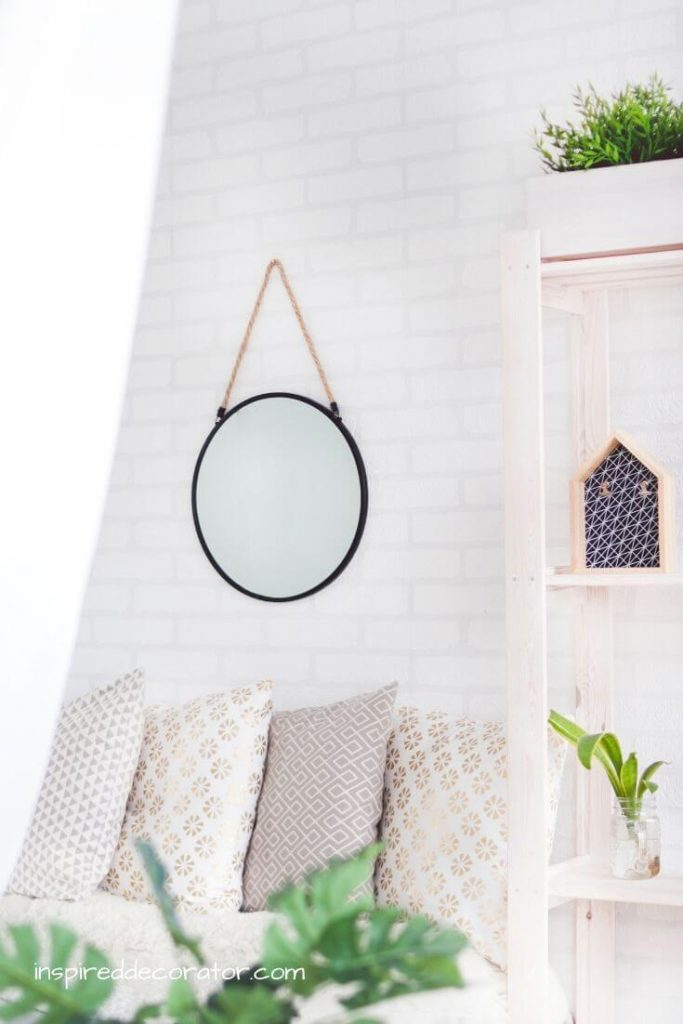 A simple room scheme consisting of a round farmhouse-inspired mirror, an assortment of soft pillows in various textures and shades of white, and a houseplant in the foreground. This is a great example of a blend of design styles used to create your own personal design style signature look. Find your own design style by learning about the top design styles and how to blend them.