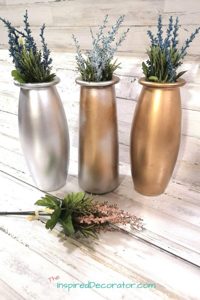 Give boring clear glass vases new life with a simple facelift using spray paint. After their makeover, these metallic jars can now be used in so many ways for different holidays and seasons. - the Inspired Decoratorflower vases with some spray paint. The options are endless for making them match your design style and color accents. - the Inspired Decorator