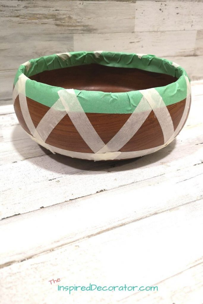 Tape off the pattern you'd like to paint on your wood bowl. Painters tape offers a good seal and won't leave residue behind after your bowl is painted. - the Inspired Decorator