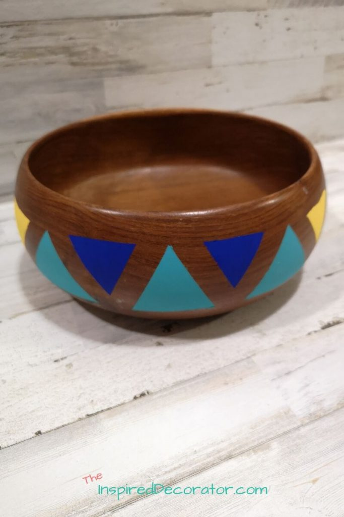 Make this easy DIY thrift flip project using an old wood salad bowl to create a succulent planter. Use painters tape and acrylic paint in color block on your wood bowl to create a beautiful print on your new succulent planter. - the Inspired Decorator