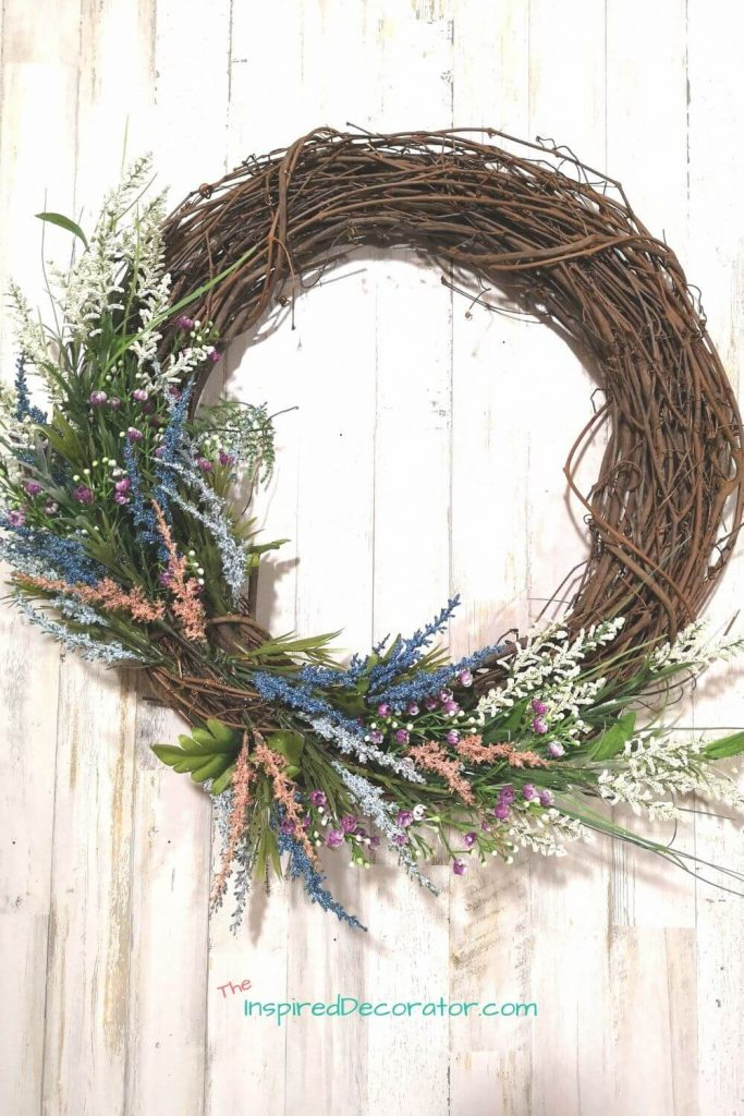 Take your time placing each floral piece into your wreath. It's fine to move them aroudn until you find the right spot. This wreath currently has all the foliage, filler and accent pieces in place, but waiting for the focal poit flower.- the Inspired Decorator