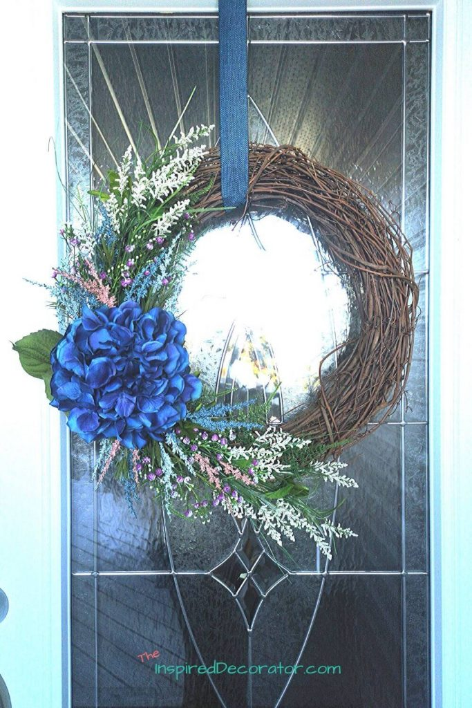 A bright blue hydrangea wreath hangs on the front door. It's a welcoming sight during summer.