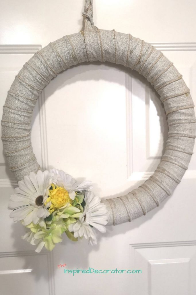This DIY burlap wreath has held up strong over the years. It's been sun-bleached but not worn out. There is a hook built into it for the flowers to be switched out seasonally.- the Inspired Decorator