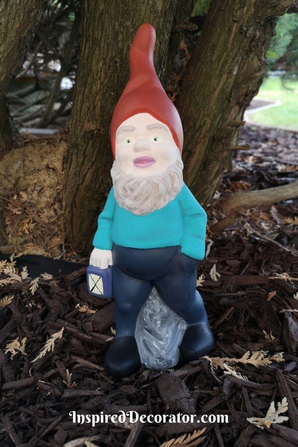The Lantern Garden Gnome looks fashionable in a brick red hat, turquoise shirt, and navy pants. The lantern he holds now has a soft glow to it. His eyes were painted green and his beard is a mix of brown and white.