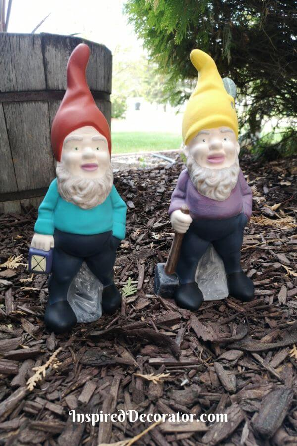 Restored hand-painted garden gnomes looks bright and cheery in the garden. The garden gnome with the lantern was painted wearing a red hat and turquoise shirt. The garden gnome with the sledgehammer was painted wearing a yellow hat and a purple shirt. Both are wearing dark blue pants and black shoes, but one has blue eyes and the other has green eyes. These details add character to theantique garden gnomes.