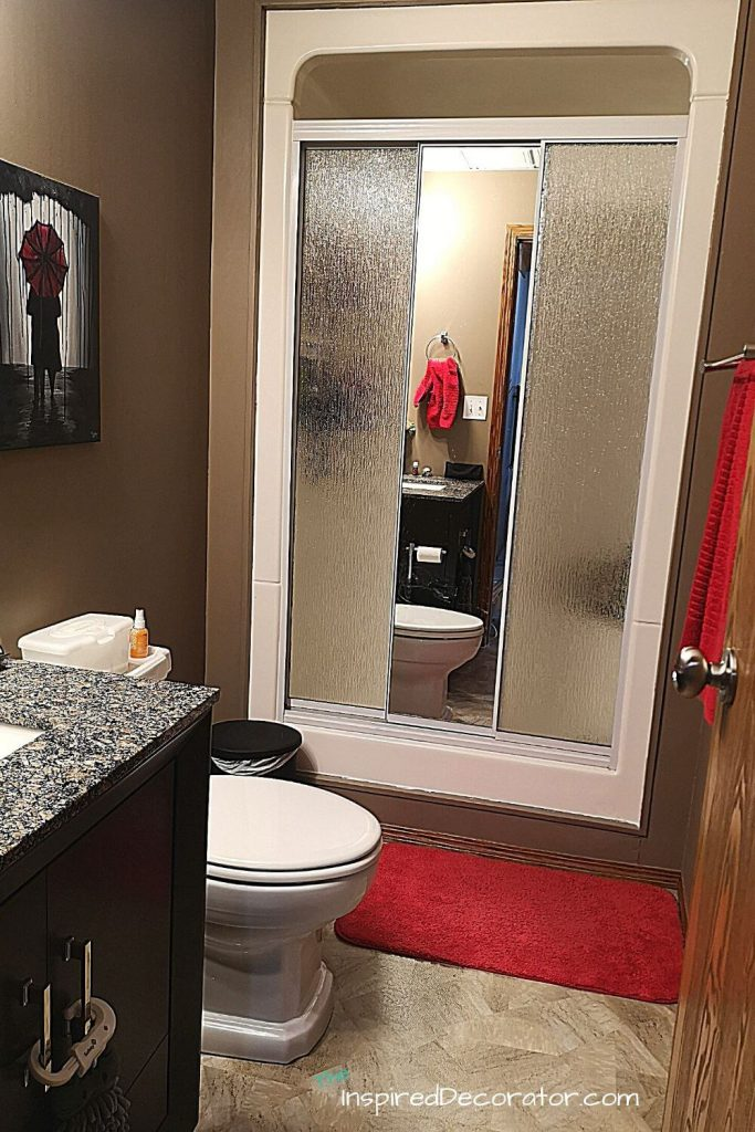 Bathroom Project Before was painted a chocolate brown and used red towel and bath mats for an accent color.