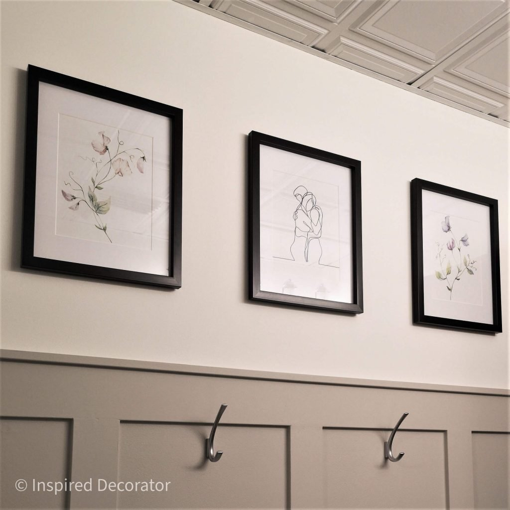 A trio of watercolor art combine the homeowners love of botanical prints and continuous line art. They are framed in dark brown frames to match the mirror above the sink.- the Inspired Decorator