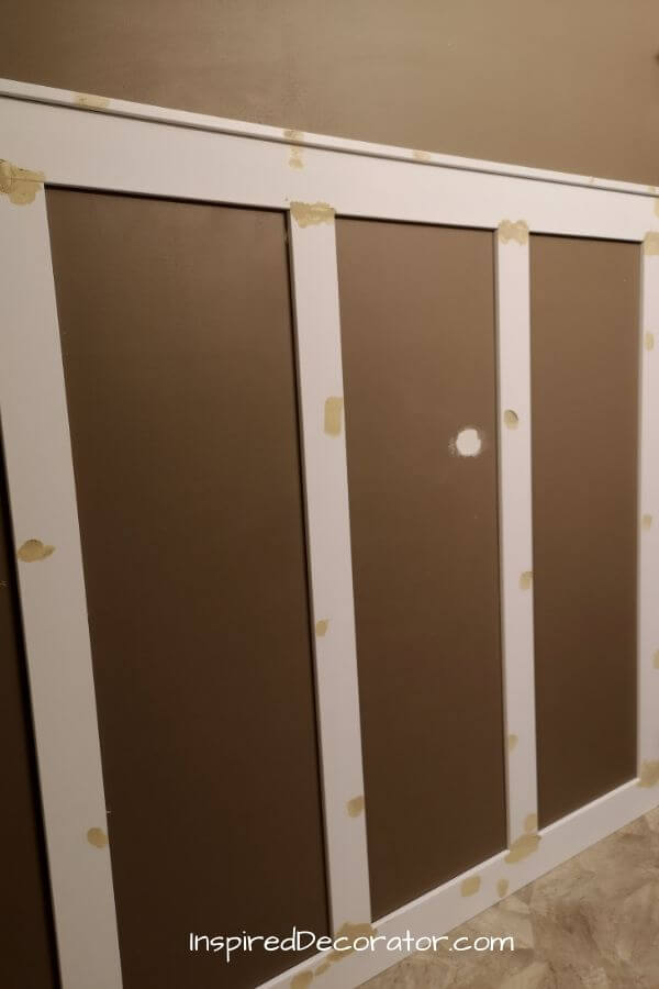 Use paintable wood filler to cover every nail hole and board gap. After painting, your boards will look like a solid piece or wainscoting.