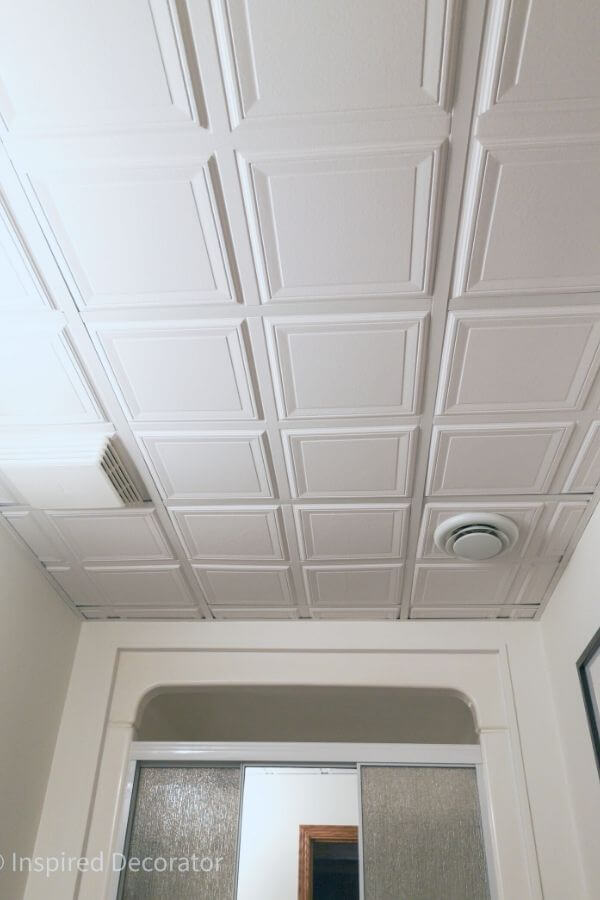 The suspended ceiling of the bathroom uses 3D ceiling tiles for added texture and interest. - the Inspired Decorator