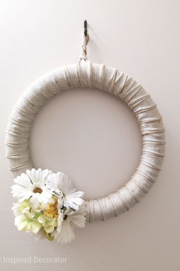 A close up view of the  DIY burlap wreath that hangs in the bathroom. It is sun-bleached but stilling holding up strong. There is a cluster of white daisies, green hrandragea blossoms, and a yellow carnation near the bottom of the wreath. - the Inspired Decorator