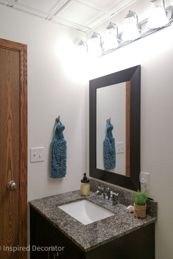 The light fixture was cleaned up and reused in the bathroom. IT coordinates with the chrome faucet of the sink below. The dark vanity and framed mirror compliment the dark frames of the bathroom art on the opposite wall. - the Inspired Decorator