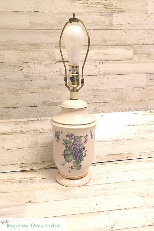 An outdated ceramic table lamp featuring gold trim and a hydrangea motif is about to get a spray-paint makeover.
